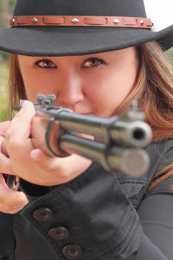 Belle cow-girl orientant le fusil photos stock