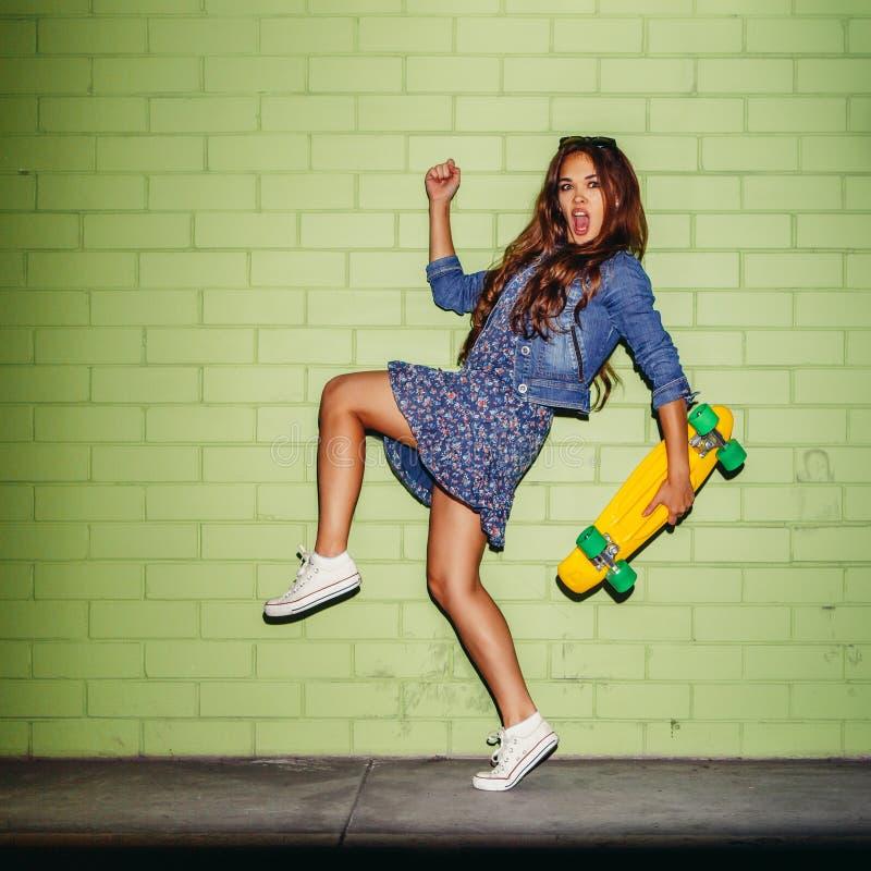 Belle dame aux cheveux longs avec un shortboard de penny de couleur près d'a photos stock