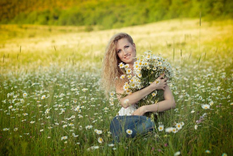 Belle dame avec la fille mignonne sur le champ de camomille photos stock