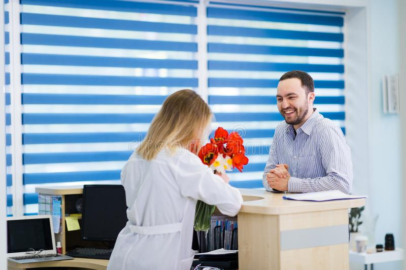 Belle dame d'infirmière flirtant avec un client masculin beau Il a apporté ses fleurs pour fonctionner photographie stock libre de droits