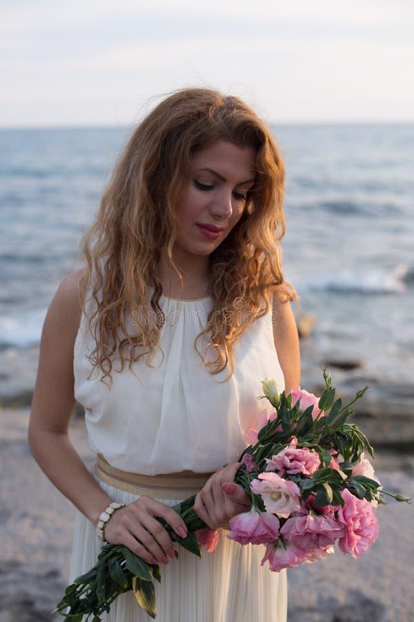 Belle dame dans la robe ene ivoire tenant le bouquet et regardant la BO photo stock
