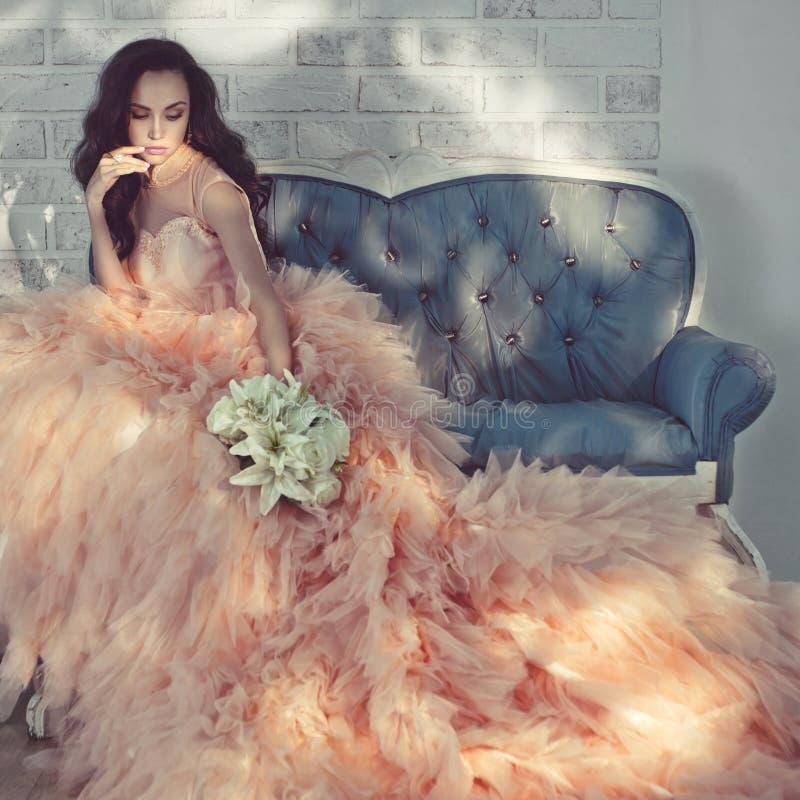 Belle dame dans la robe magnifique de couture sur le sofa photographie stock libre de droits