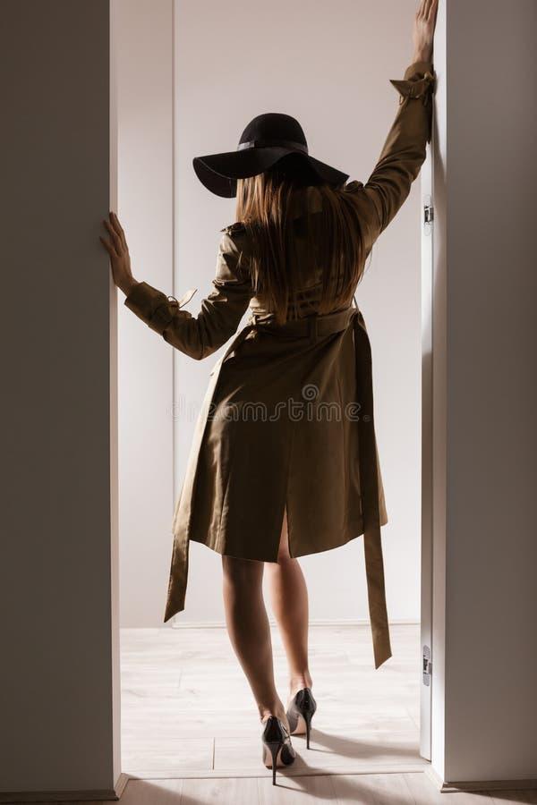 Belle dame dans le manteau de fossé, le chapeau et des chaussures noires sur des talons se tenant de son dos photographie stock