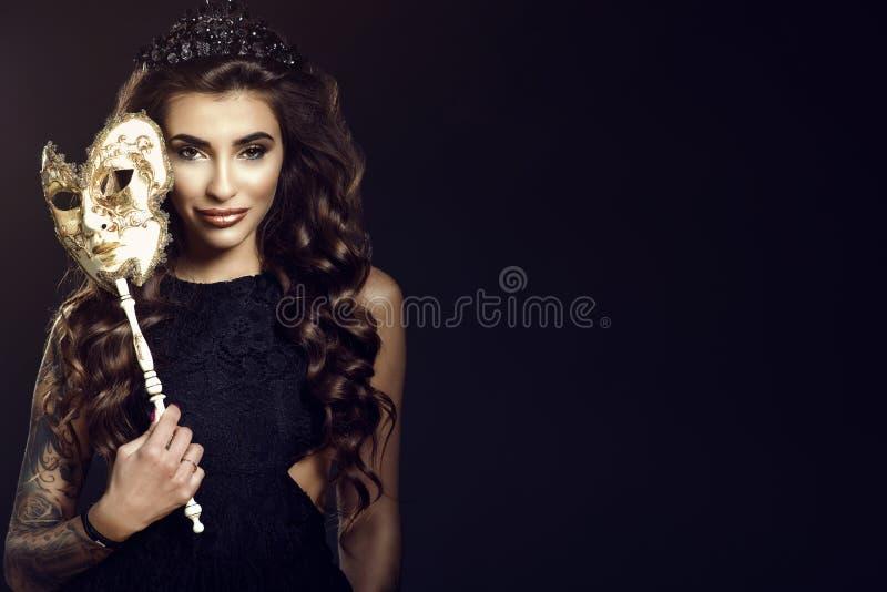 Belle dame de sourire tatouée dans la couronne de bijou tenant un masque vénitien dans sa main images libres de droits