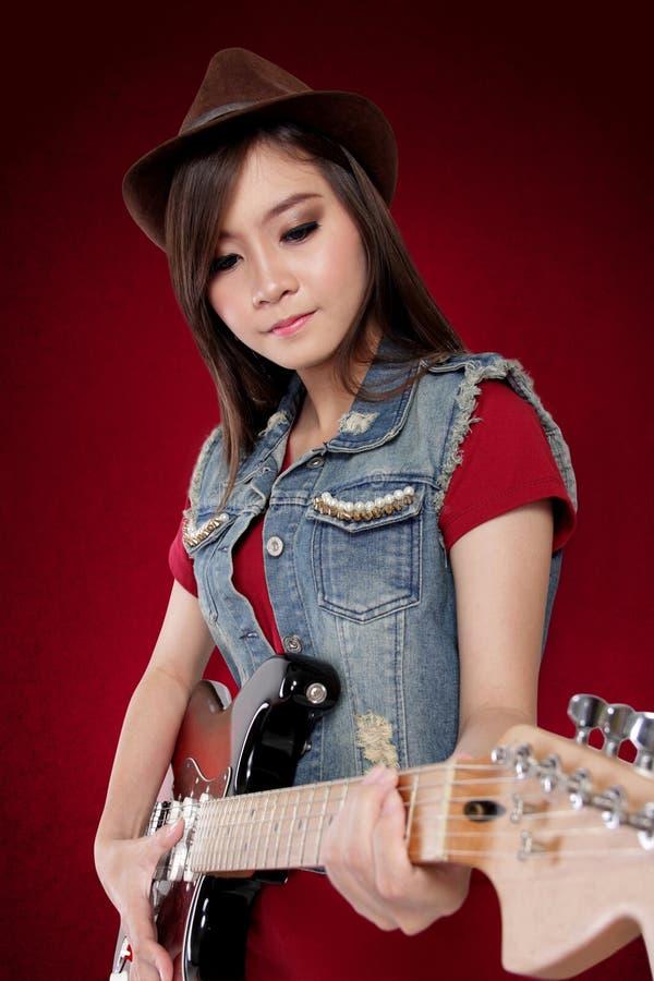Belle dame en rouge basculant sa guitare image stock