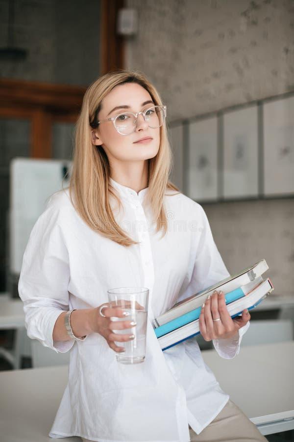 Belle dame en verres se tenant avec le verre de l'eau et de livres dans des mains Jeune dame avec le blanc de port de cheveux blo images libres de droits