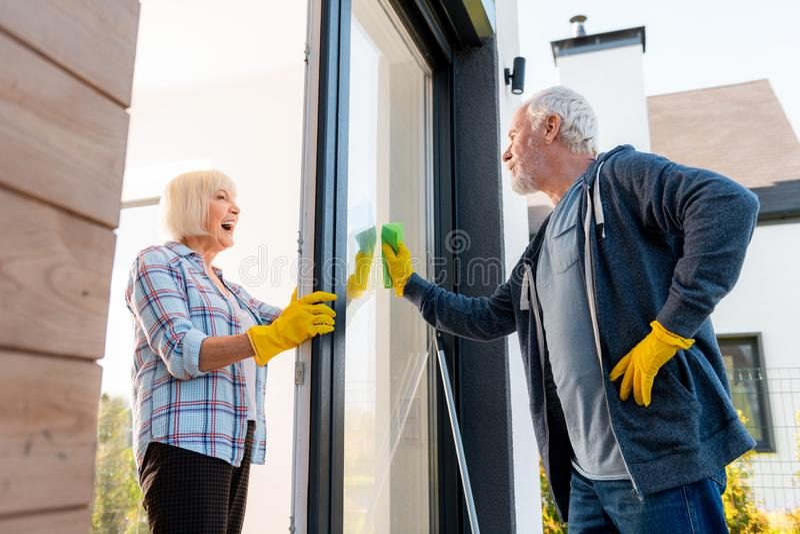 Belle dame pluse âgé se sentant positive tout en nettoyant des portes avec son mari images stock