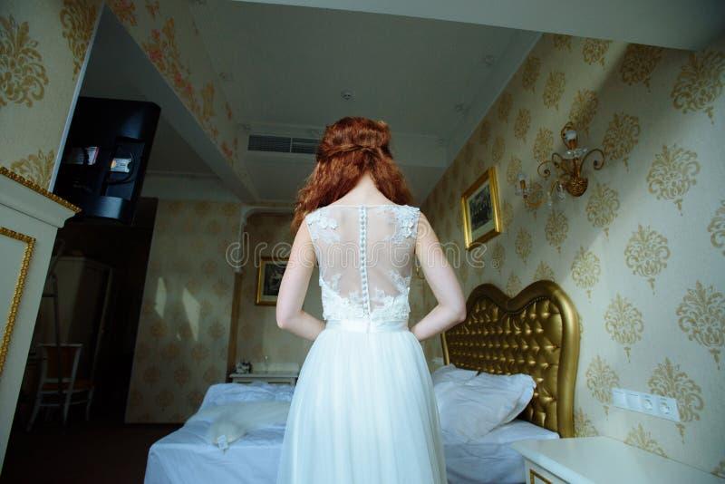 Belle dame sexy de redhair dans la robe de mariage blanche élégante Portrait de mode de modèle à l'intérieur Position de femme de photo libre de droits
