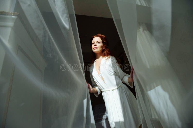 Belle dame sexy de redhair dans les culottes et le peignoir blancs élégants Portrait de mode de modèle à l'intérieur Femme de bea image libre de droits