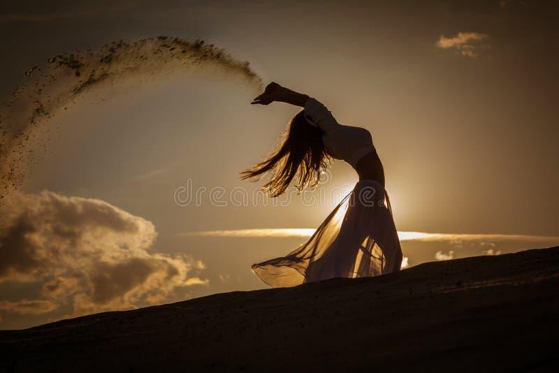 Belle danse de femme au coucher du soleil d'or image stock