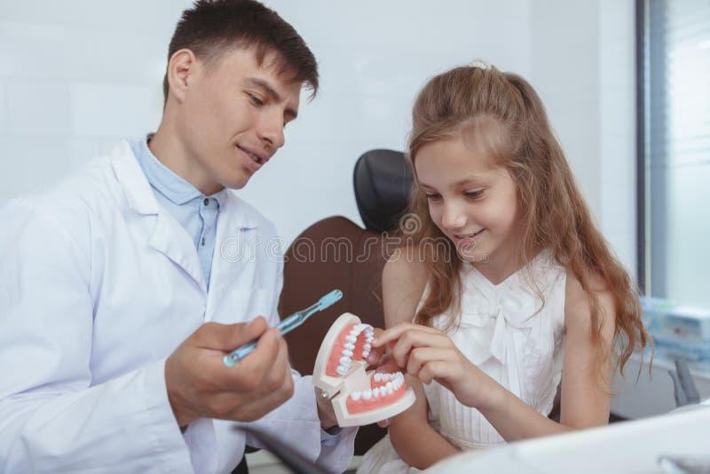 Belle dentiste de visite de jeune fille image stock