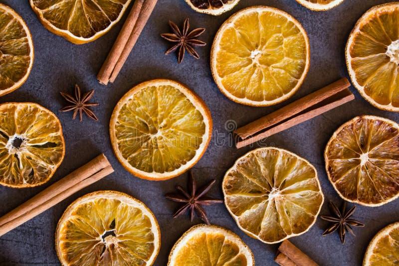 Belle disposition étendue plate de vue supérieure des bâtons de cannelle d'oranges et de l'anis d'étoile secs sur le fond gris-fo photos stock