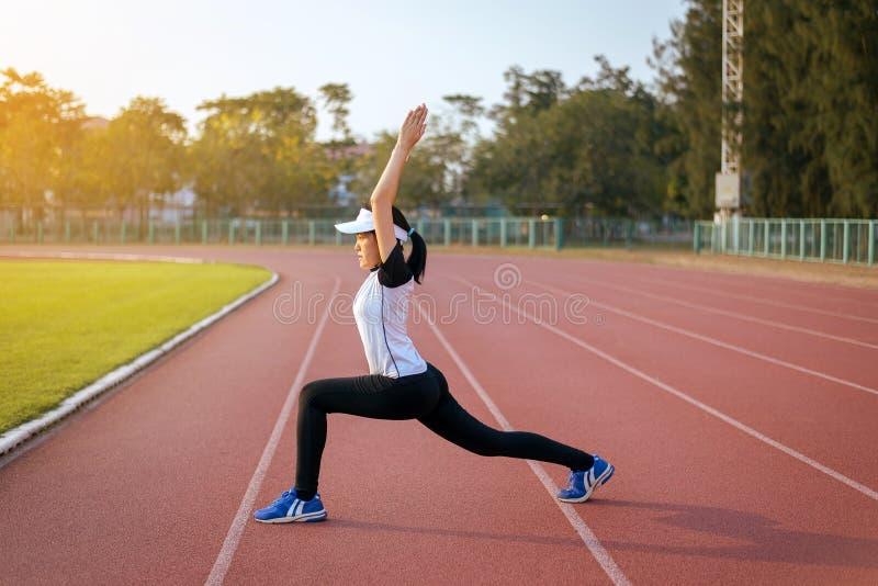 Belle donne asiatiche che allungano e che si scaldano prima dell'correre o del risolvere alla pista all'aperto di mattina immagine stock