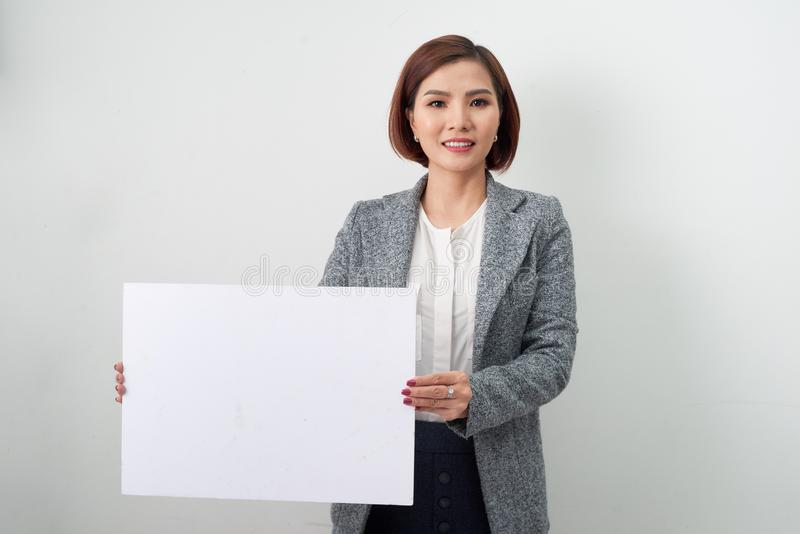 Belle donne asiatiche tenere e mostrare pubblicità di carta in bianco bianca sul fondo bianco fotografie stock