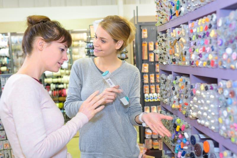 Belle donne che comperano nel supermercato e che decidono che cosa comprare immagine stock libera da diritti
