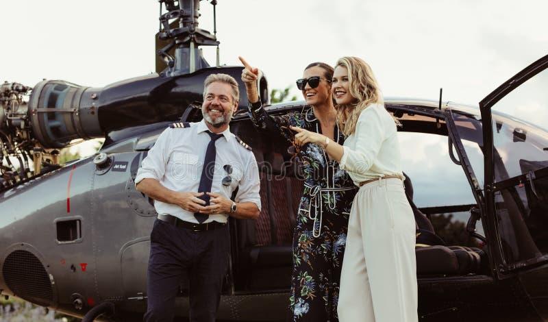 Belle donne che fanno una pausa elicottero con il pilota fotografia stock libera da diritti