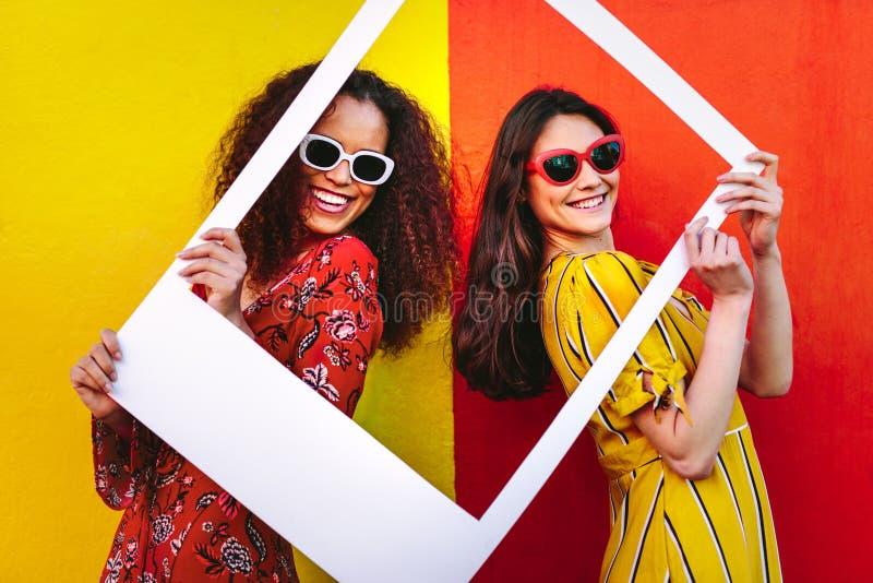 Belle donne che tengono una struttura in bianco della foto fotografia stock libera da diritti