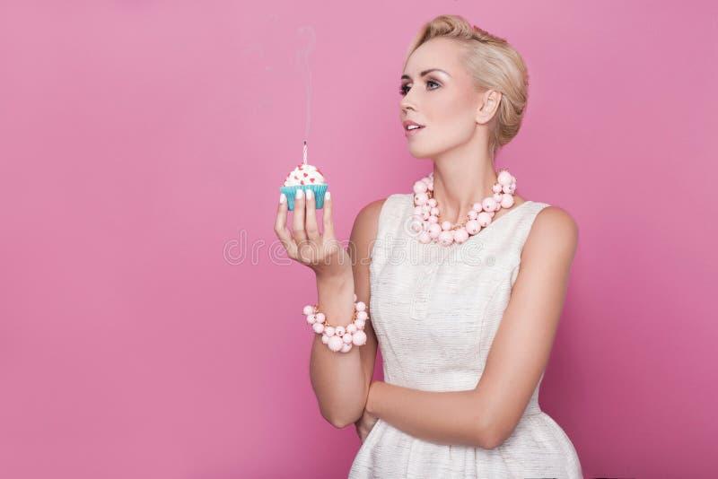 Belle donne con il vestito crema che tiene piccolo dolce con la candela variopinta Compleanno, festa fotografia stock libera da diritti