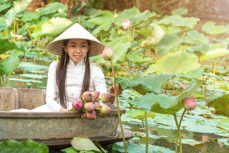 Belle donne dell'Asia che portano il cappello tradizionale bianco del vestito Ao Wai del Vietnam e dell'agricoltore del Vietnam e fotografia stock