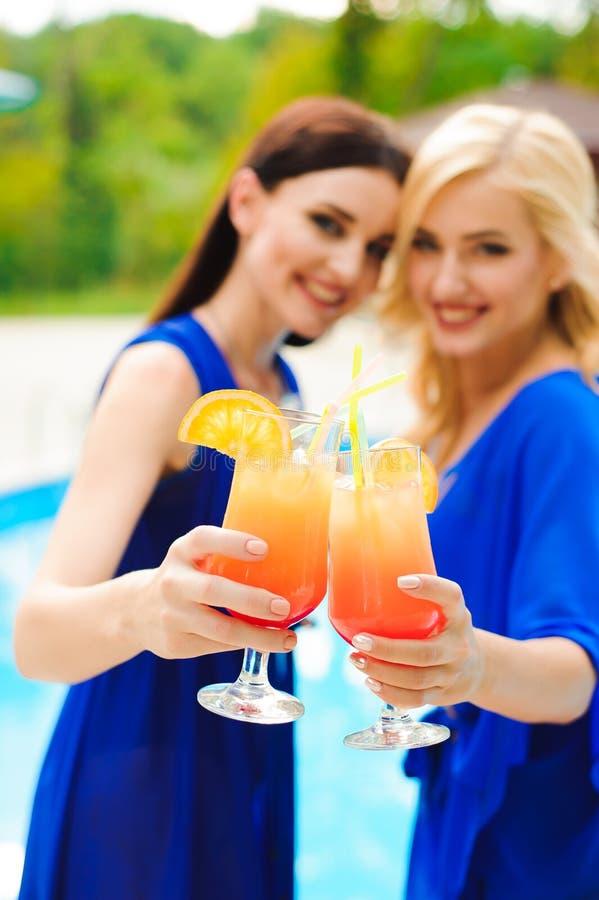 Belle donne sexy in bikini che bevono un attimo dei cocktail che si rilassa nella piscina fotografia stock