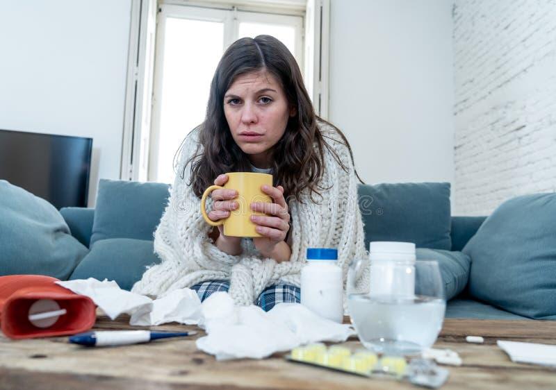 Belle douleur de femme du froid prenant ? sentiment chaud de m?decine de boissons le malade terrible ? la maison image libre de droits