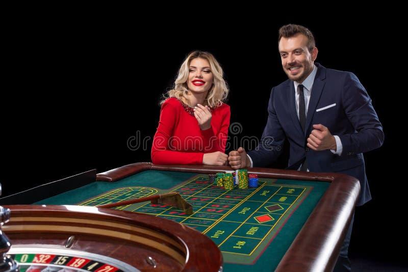 Belle e coppie ben vestito che giocano roulette nel casinò immagini stock libere da diritti