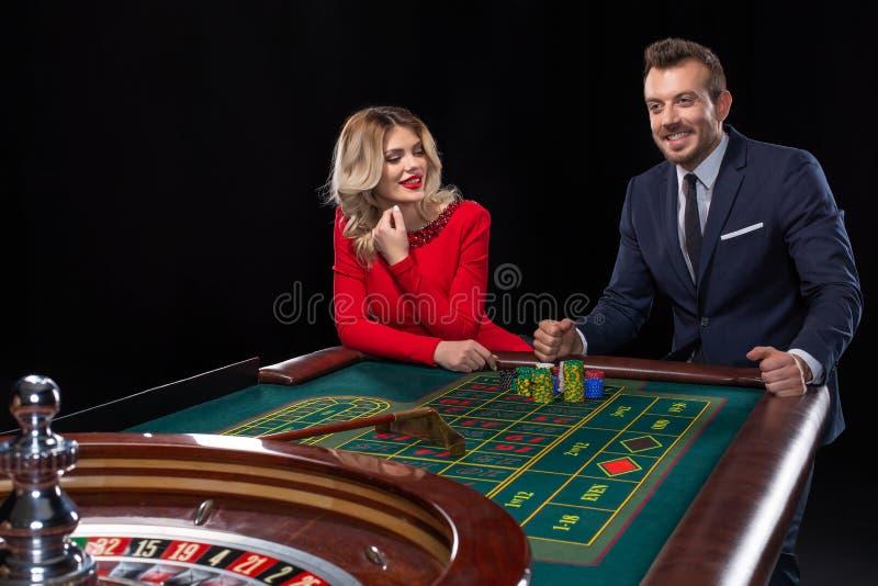 Belle e coppie ben vestito che giocano roulette nel casinò immagini stock
