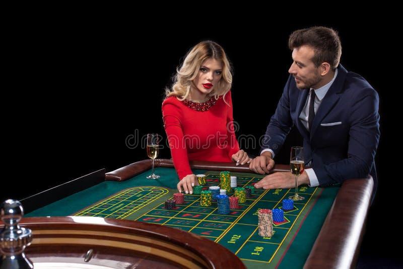 Belle e coppie ben vestito che giocano roulette nel casinò immagine stock libera da diritti