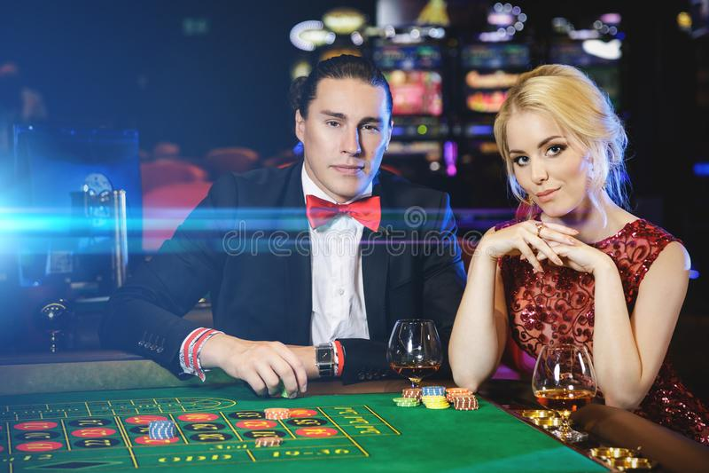 Belle e coppie ricche che giocano roulette nel casinò fotografie stock libere da diritti
