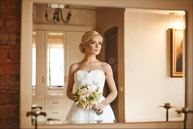 Belle et à la mode fille modèle blonde avec la coiffure de mariage dans la robe à la mode avec le bouquet des fleurs dans des  images libres de droits