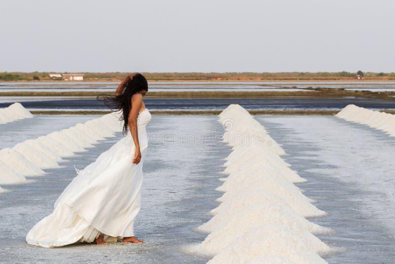 Belle et élégante jeune mariée avec la longue robe blanche marchant dans le domaine de sel entouré par des tas de sel, paniers tr photos libres de droits