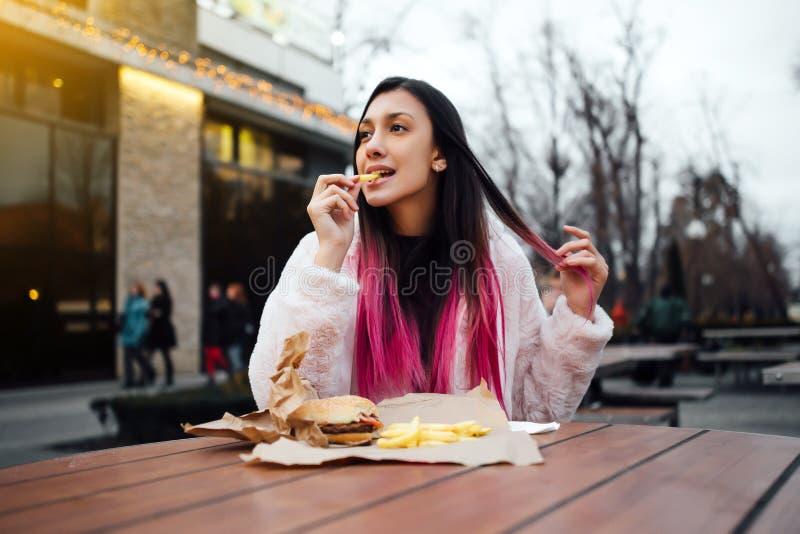Belle et gaie fille mangeant un hamburger juteux et des pommes frites sur la rue images stock