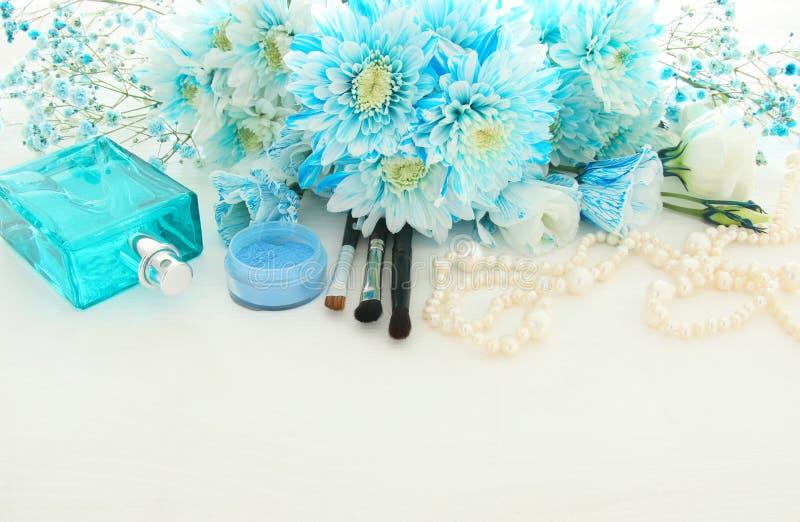 belle et sensible disposition de fleurs bleue à côté de collier de perles, de parfum frais et de maquillage photos libres de droits