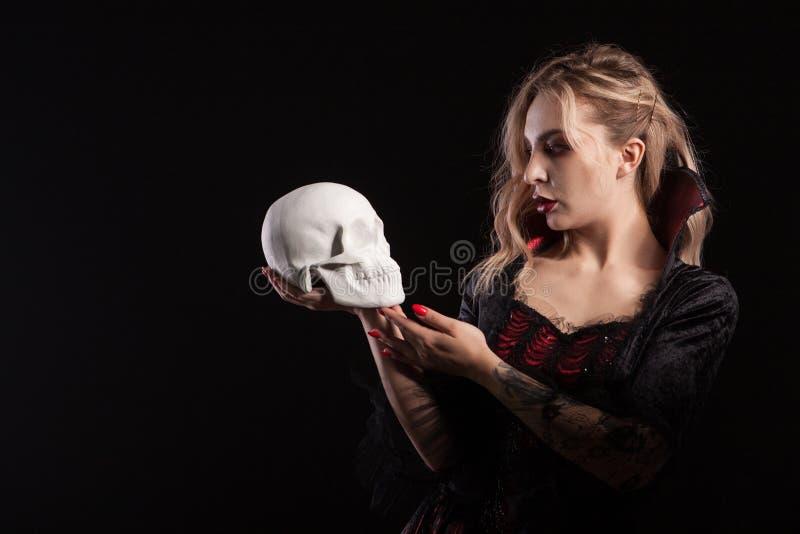Belle et sexy femme blonde habillée comme une tenue de vampire et regardant un crâne image stock