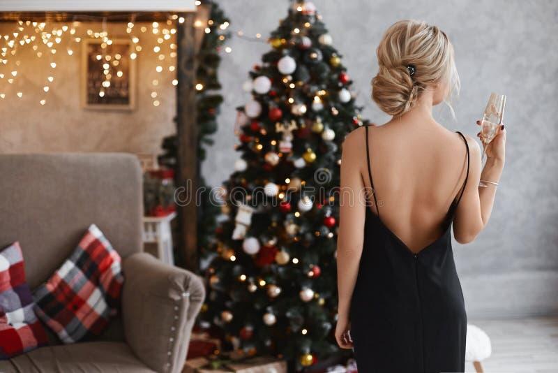 Belle et sexy jeune fille modèle blonde avec un corps parfait dans la robe noire avec le dos nu garde un verre de champagne et images stock
