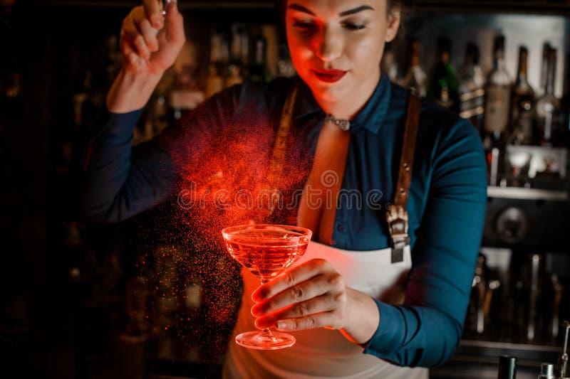 Belle et sexy pulvérisation femelle de barman amère sur le verre de cocktail élégant photos stock
