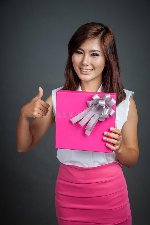 Belle exposition asiatique de fille un boîte-cadeau et pouces  photographie stock libre de droits