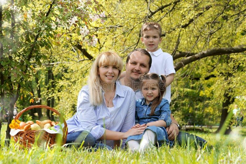 Belle famille avec des enfants ayant le pique-nique dehors photo stock