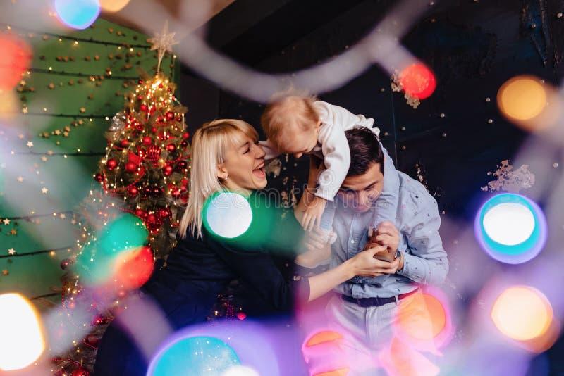 Belle famille avec peu de bébé sur le fond d'un arbre de Noël, célébrant la nouvelle année photographie stock libre de droits