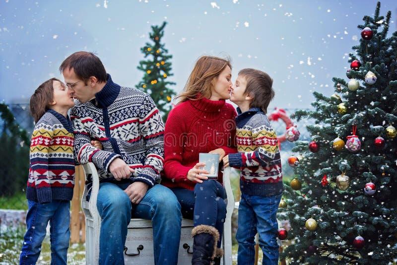 Belle famille de quatre heureuse, ayant l'amusement dehors dans la neige photo libre de droits