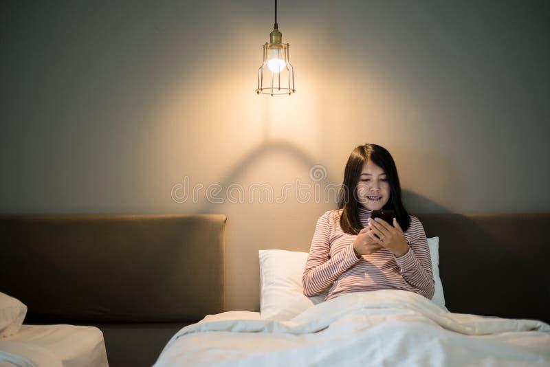 Belle femelle asiatique utilisant le t?l?phone intelligent sur le lit ? de fin de nuit, aux maladies oculaires et au concept de d photo libre de droits