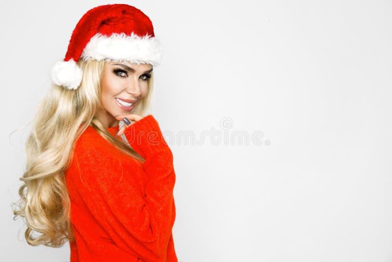Belle femelle blonde sexy et souriante habillée dans un chapeau de Santa Claus Fille sensuelle de beauté pour Noël photos stock