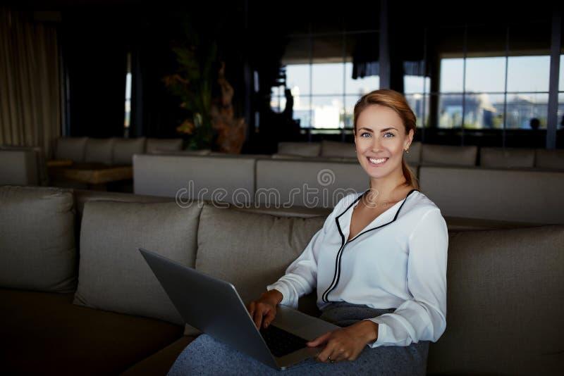Belle femelle dans la bonne humeur travaillant au filet-livre tout en attendant l'ordre dans l'intérieur moderne de restaurant images libres de droits