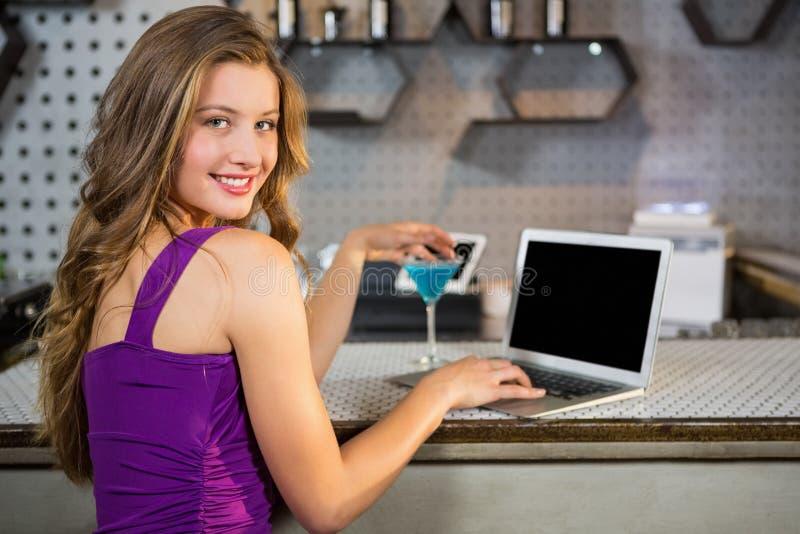 Belle femme à l'aide de l'ordinateur portable tout en ayant le cocktail photographie stock