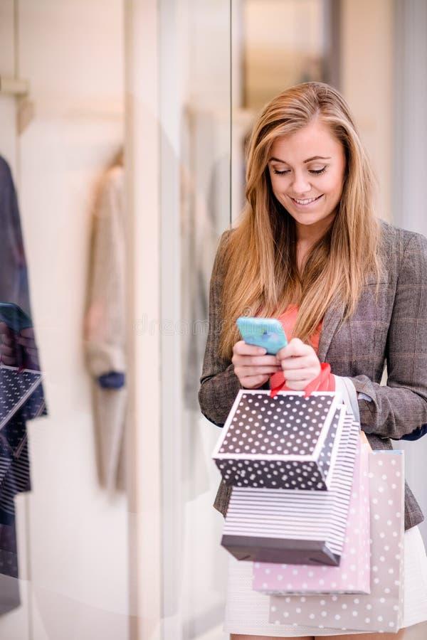 Belle femme à l'aide de son téléphone tandis que lèche-vitrines images libres de droits
