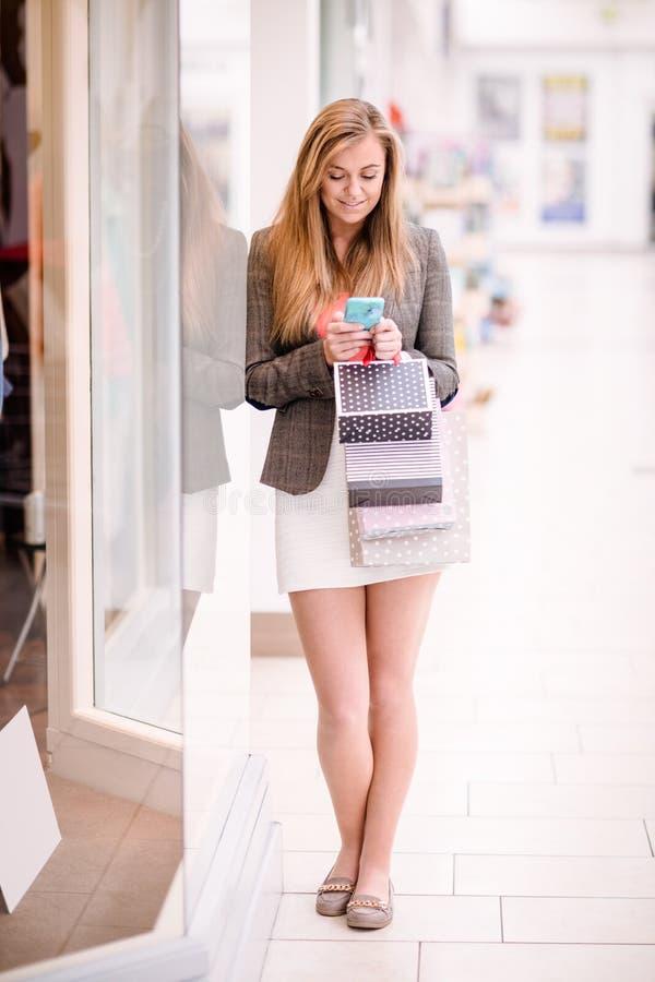 Belle femme à l'aide de son téléphone tandis que lèche-vitrines photographie stock libre de droits