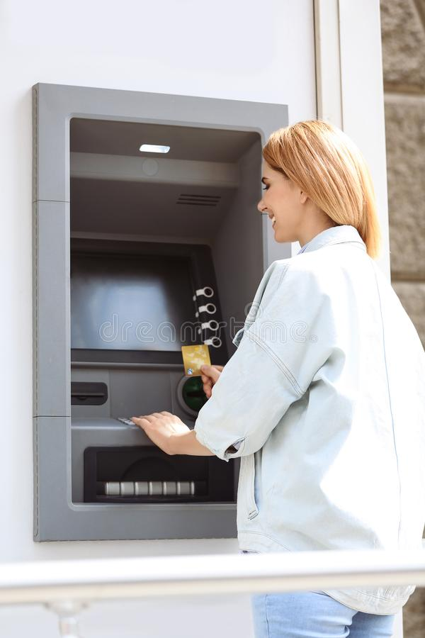 Belle femme à l'aide du distributeur automatique de billets pour le retrait d'argent photographie stock libre de droits