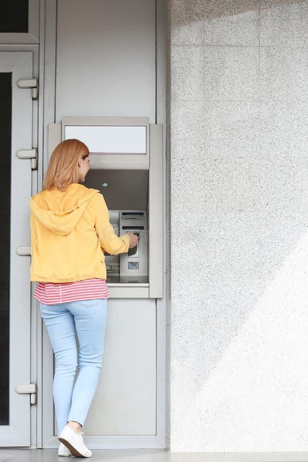 Belle femme à l'aide du distributeur automatique de billets pour le retrait d'argent dehors image libre de droits