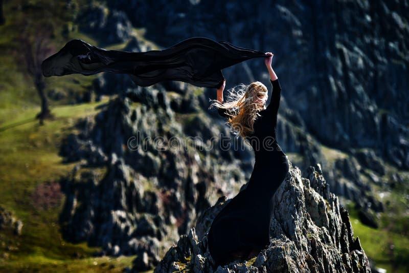Belle femme à la mode avec la robe noire extérieure photographie stock