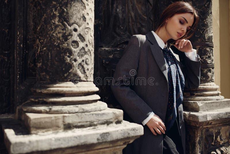 Belle femme à la mode dans des vêtements de mode posant dans la rue photos libres de droits